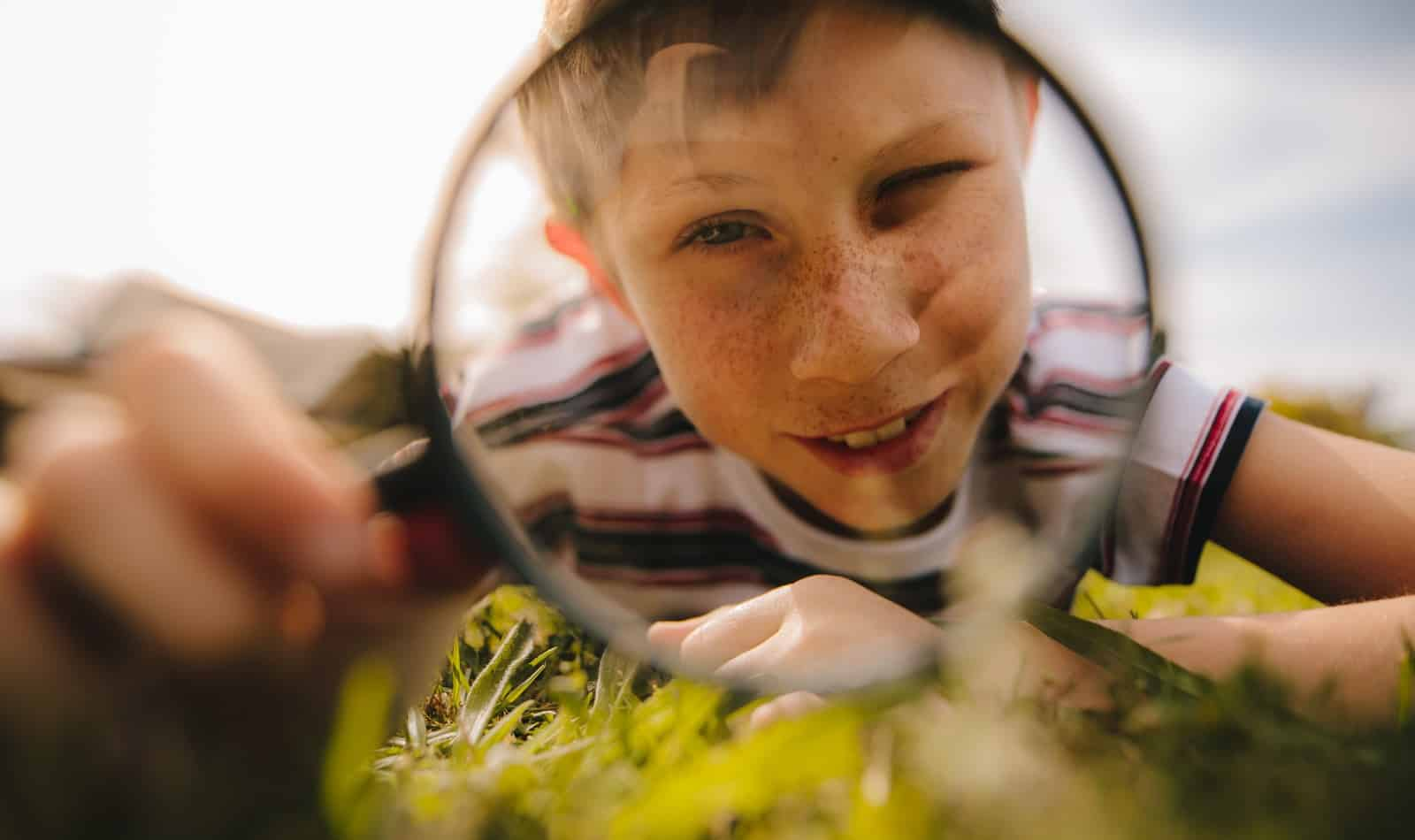 Boy looking through magnifying glass. cute boy exploring with magnifying glass.