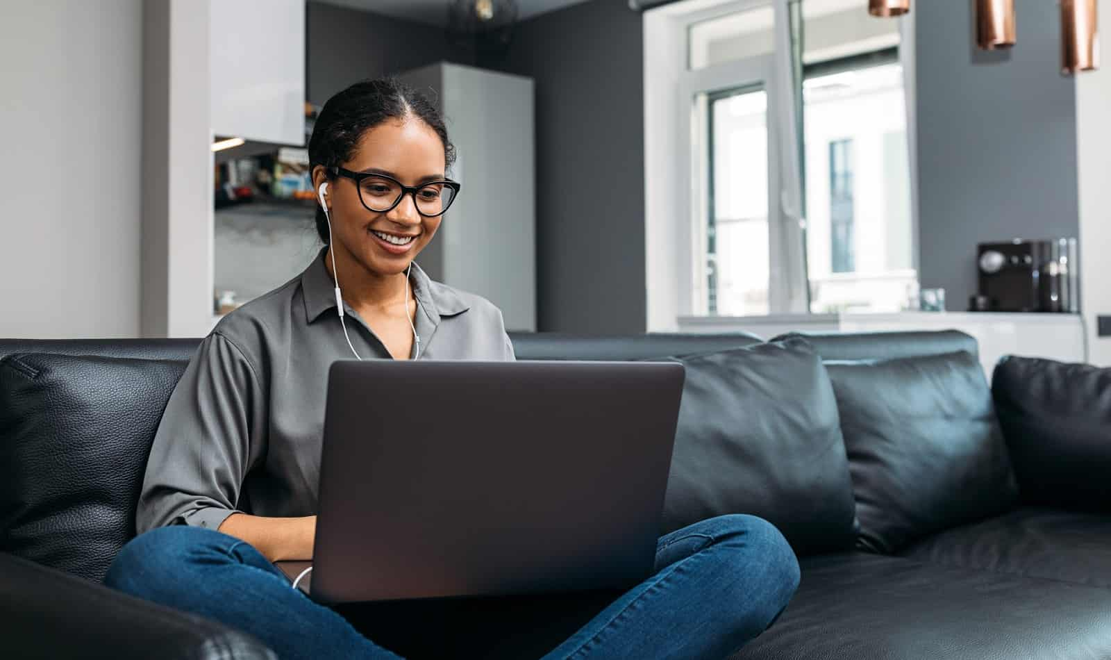 Young woman video calling using a laptop sitting on a sofa that doubles as her home office space