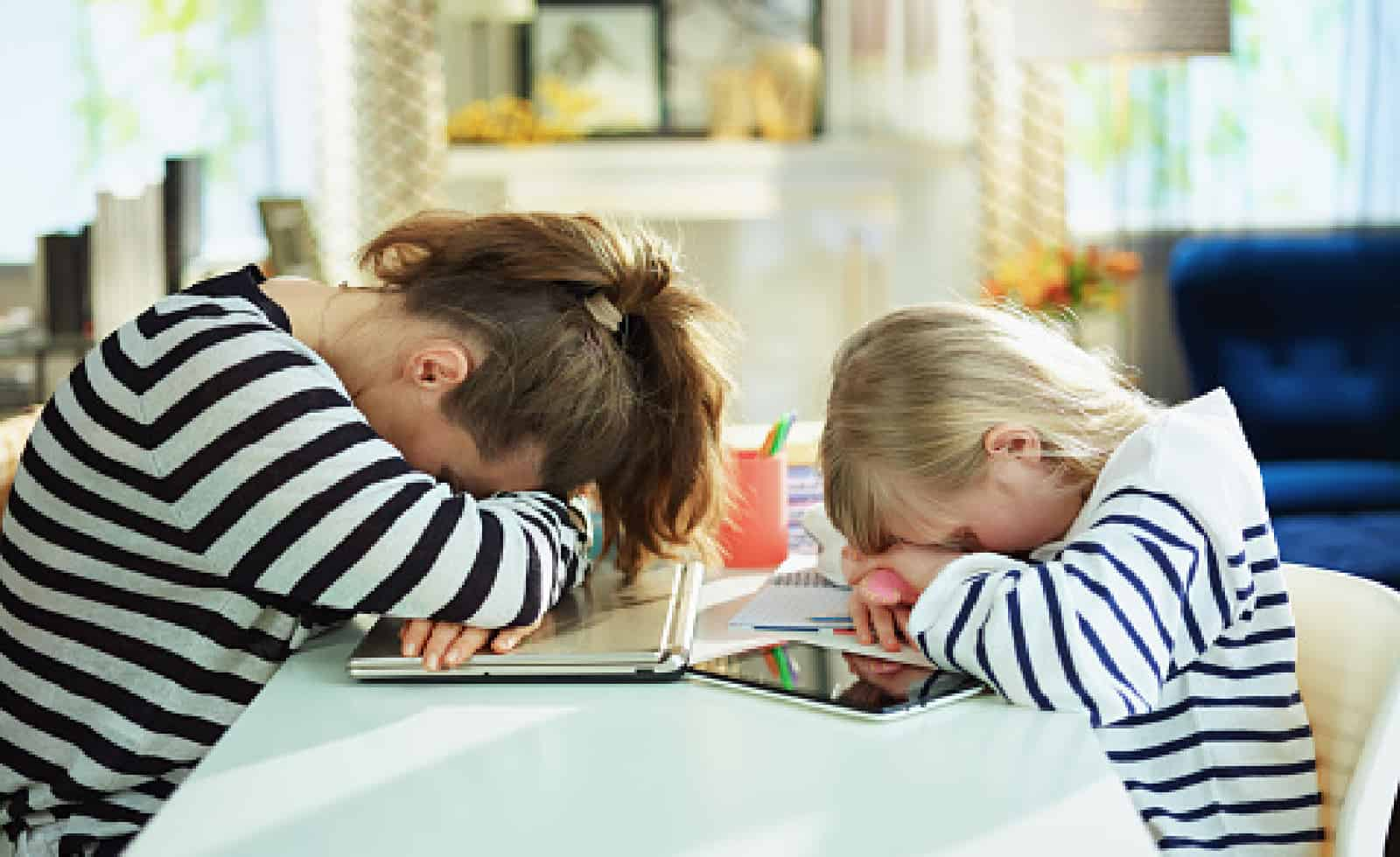 tired young mother and child in striped sweaters in home office in the modern living room in sunny day laying on table