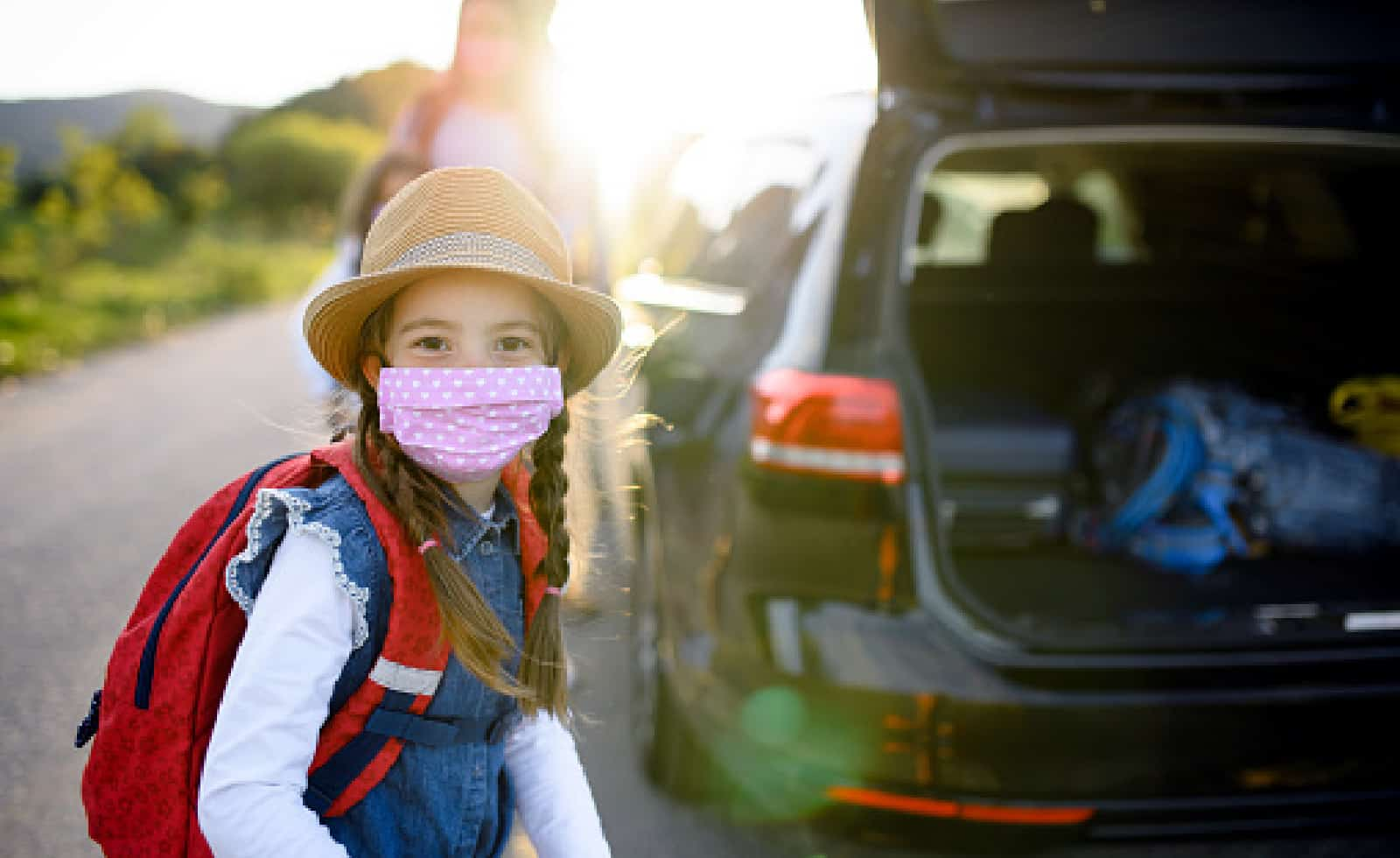 Front view of small girl with family on trip outdoors in nature, wearing face masks